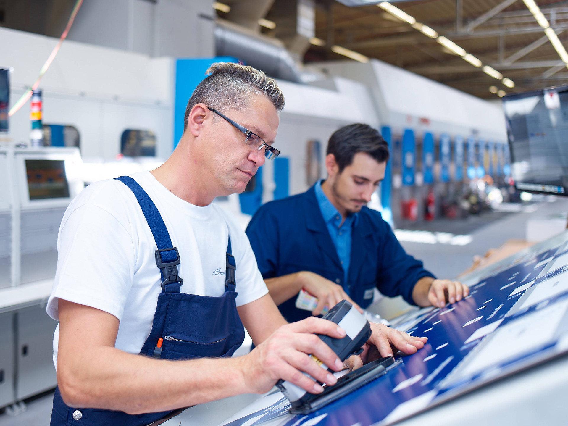 [Translate to Niederländisch:] Zwei Mitarbeiter überprüfen die Druckergebnisse des Inliner4 in der Produktion