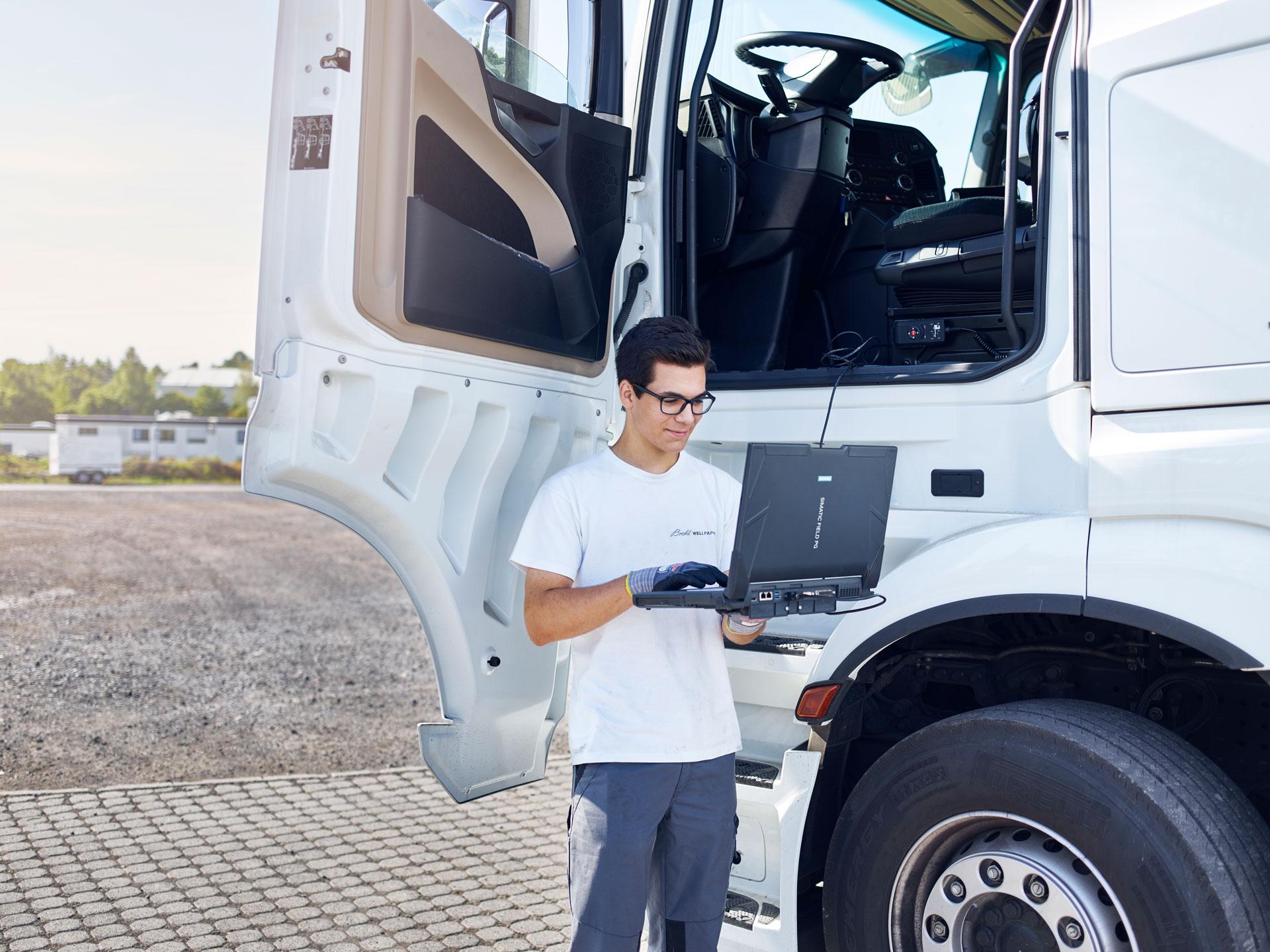 Azubi im Bereich KFZ-Mechatroniker steht in der geöffneten LKW Tür mit einem Laptop in der Hand