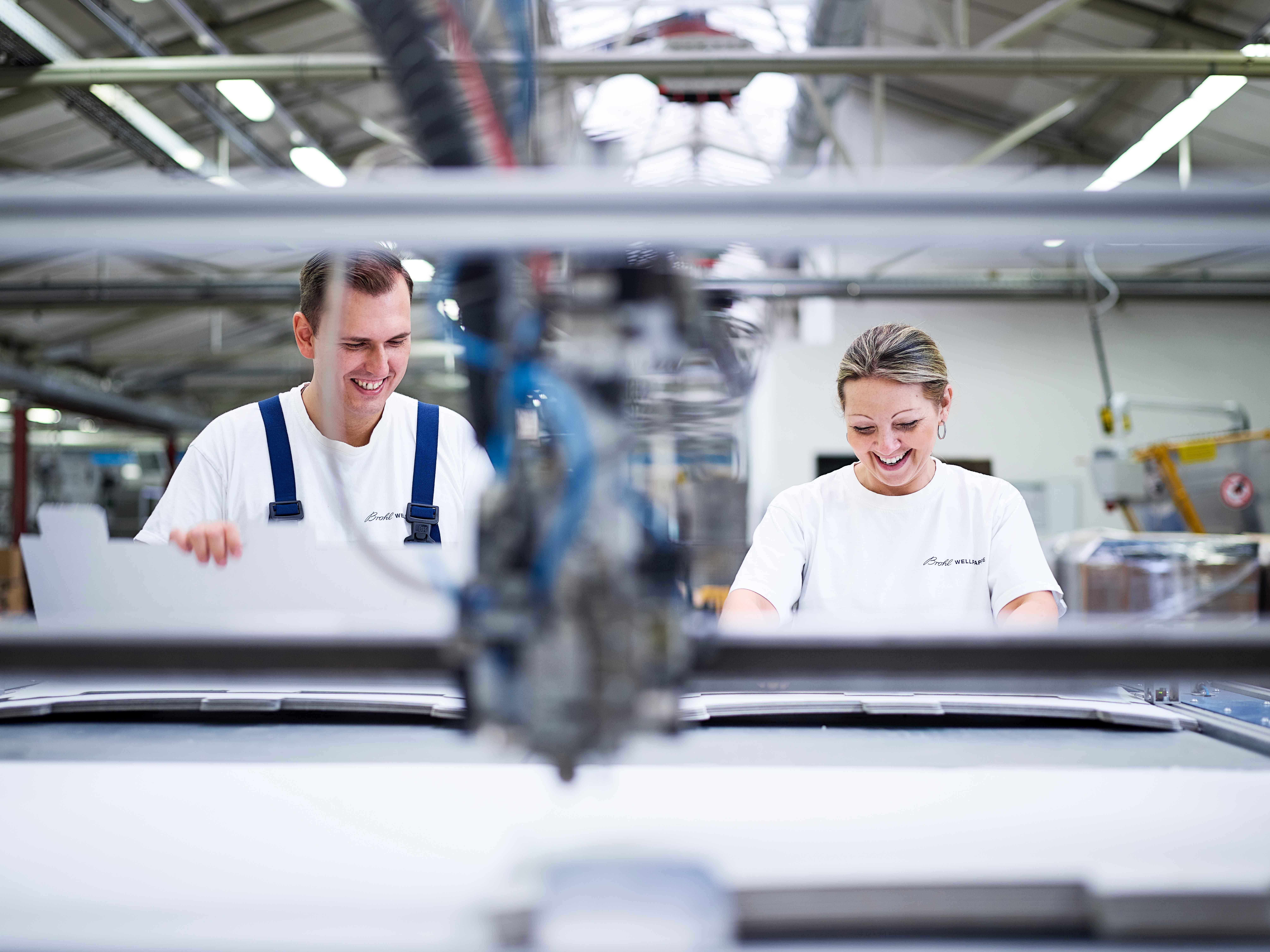Zwei Mitarbeiter arbeiten an der Klebemaschine bei Brohl Wellpappe im Werk Niederzier