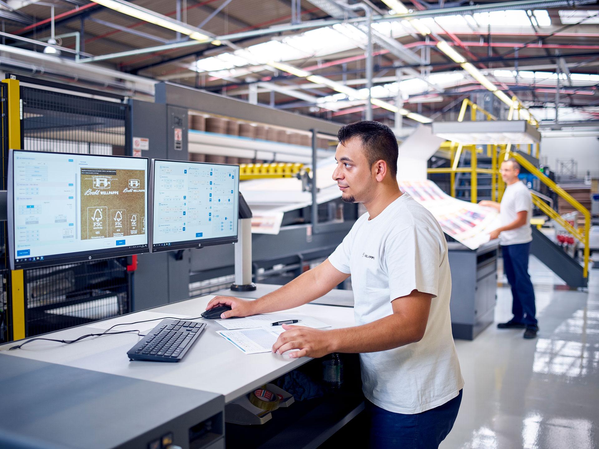 [Translate to Niederländisch:] Mitarbeiter arbeitet an der Digitaldruckmaschine