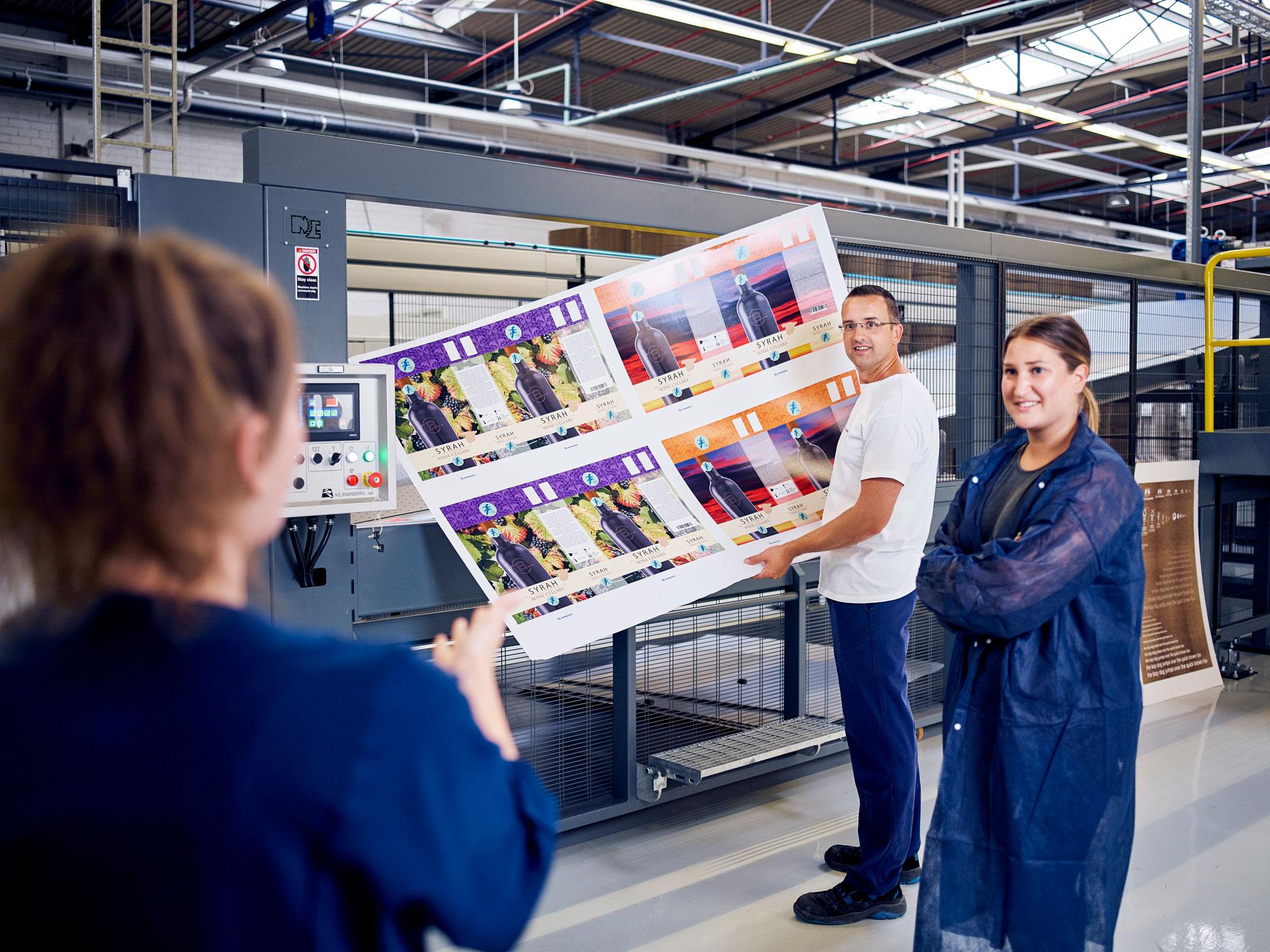 [Translate to Niederländisch:] Mitarbeiter überprüfen das Druckergebnis des Digitaldruckers