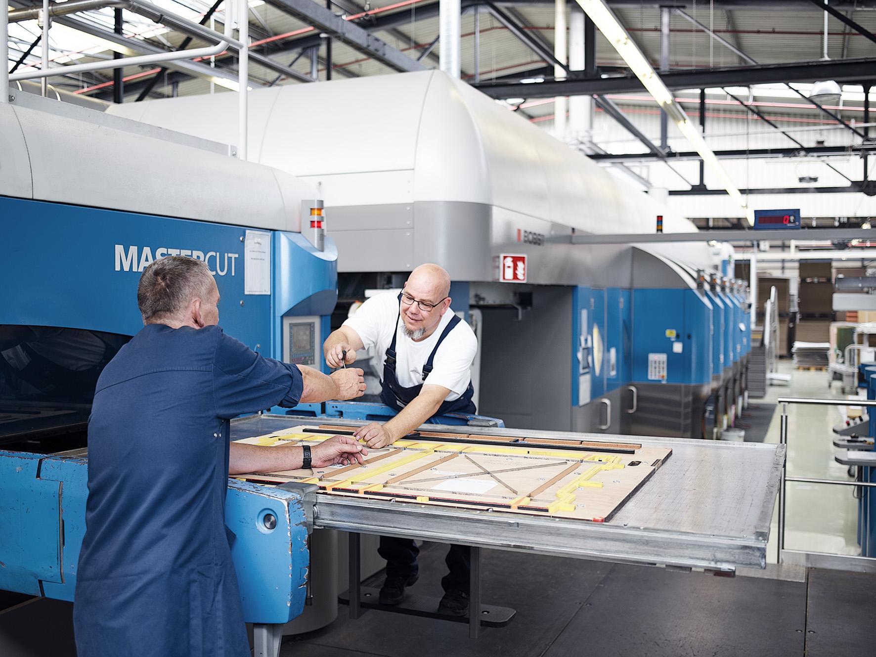 [Translate to Niederländisch:] Zwei Mitarbeiter reichen sich Werkzeuge während der Produktion